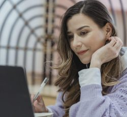 Positive woman working on laptop and taking notes