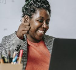 Positive black teacher showing thumb up during online test